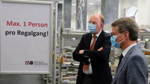 Der bayerische Kunst- und Wissenschaftsminister Bernd Sibler (r.) überzeugt sich zusammen mit dem Generaldirektor der Bayerischen Staatsbibliothek Dr. Klaus Ceynowa (l.) von den Hygiene- und Sicherheitsmaßnahmen bei der Ausleihe